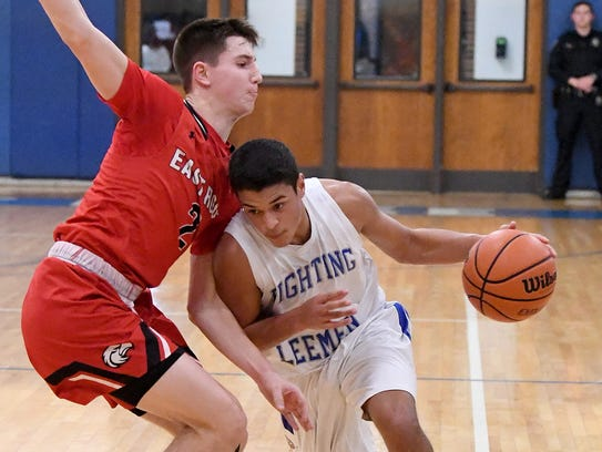 Robert E. Lee's Jayden Williams takes the ball around an East Rockingham player during the Shenandoah District boys basketball championship Feb. 16 in Staunton.