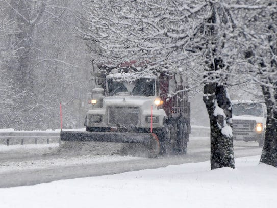 A snowplow travels with blade down on U.S. 250 just