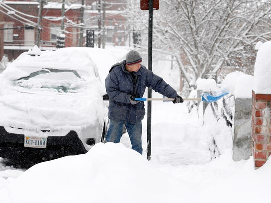 A man shovels snow clear of the sidewalk in front of