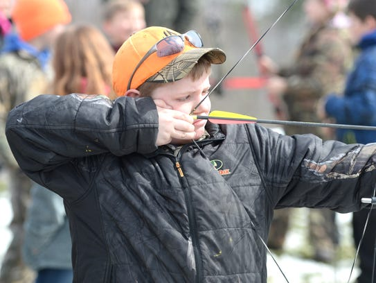 Austin Painter, 10, takes his turn at the archery station