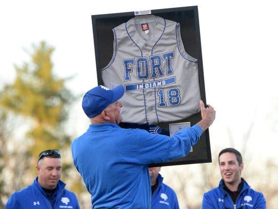 Vic Spotts holds up a shadow box with the jersey he