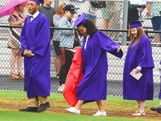 One graduate smiles as she looks down to her shoes