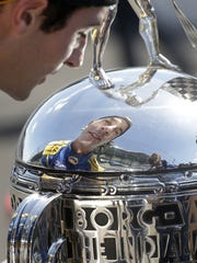 IndyCar driver Alexander Rossi moves in Monday to kiss the Borg-Warner Trophy.