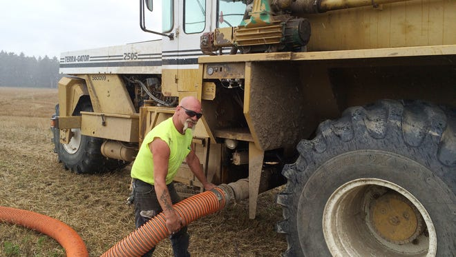 Mike Nickell fills his Terra-Gator truck with bio-solids from a tanker.