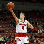 University of Louisville's Dillon Avare (4) fights to get his shot off under pressure from Jacksonville State's defense during the second half at the KFC Yum! Center in Louisville, Kentucky.       November 17, 2014