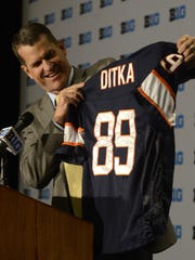July 31, 2015: Michigan head coach Jim Harbaugh shows a jersey of his former Chicago Bears coach Mike Ditka while speaking to the media during the NCAA college Big Ten Football Media Day in Chicago.