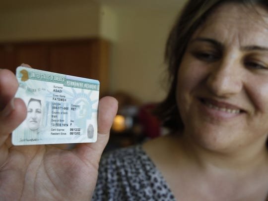 Una mujer muestra su 'green card'.