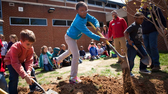 Toni Jones, 7, center, and Max Vecker, 7, left, shovel dirt onto a newly planted dogwood tree at McSwain Elementary in celebration of Arbor Day on Friday, April 24, 2015.