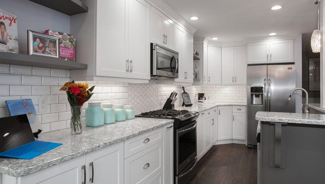 Cabinets are Statesman style in Satin White. The countertops are Cambria quartz in Berwyn to complement the Transitional-style kitchen remodel.