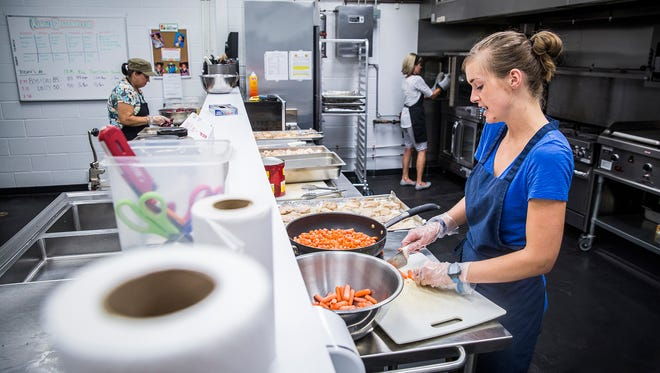 Lauren Shirey prepares meals for Boys and Girls Club members with other volunteers at Fresh Directions in Muncie Thursday afternoon.