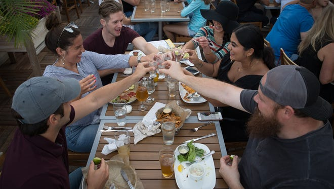 Jerome Rogers of Clinton Township, Cody Maccagnone of Clawson, Jonathan Bennett of Royal Oak, Olivia Ray of Royal Oak, Roya Yodhes of Harrison Township, and Nick Yodhes of Harrison Township toast before taking a tequila shot at HopCat in Royal Oak, Mich. on Friday, July 20, 2018.