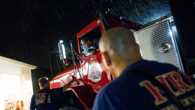 Captain Jason Sellers, left, instructs Aaron Douglas, firefighter, where to park the vehicle Squad 72 as Lieutenant Manny Arroyo helps on Saturday, September 9, 2017 at the Greater Naples Fire Rescue Station 72 as Hurricane Irma makes its way towards Southwest Florida.  The firefighters made final adjustments to makes sure that gear and vehicles were in the proper place to deploy after the storm. Squad 72 will be used as a light and air vehicle.