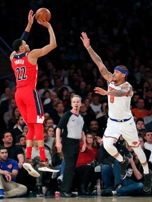 Washington Wizards forward Otto Porter Jr. (22) shoots a three-pointer as New York Knicks forward Michael Beasley (8) defend in the second half of an NBA basketball game in New York, Wednesday, Feb. 14, 2018. The Wizards defeated the Knicks 118-113.