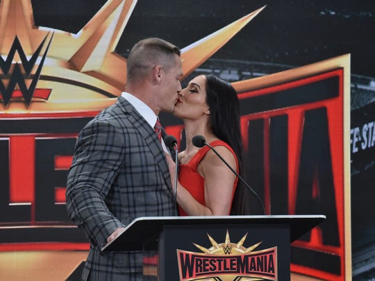 Wrestler John Cena kisses his wife and a wrestler Nikki Bella at the press conference