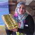 A participant in the Syrian Sweets Exchange program poses for a photo  with her creations at the Middle Easter Bakery and Deli in Phoenix.