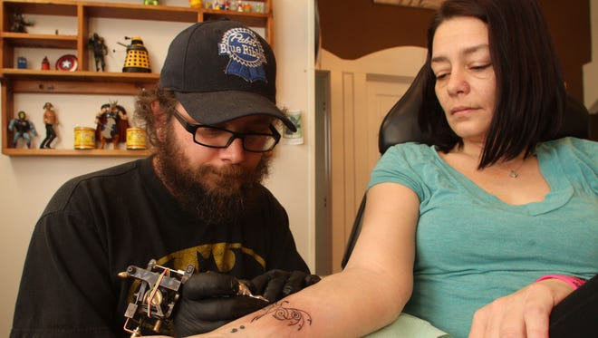 Client Magen LaFave, right, gets a Pheonix tattoo by tatooist Darl Papple of The Shop in Fowlerville.