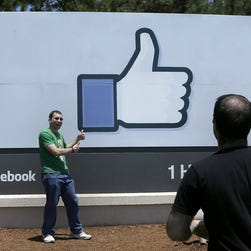 n this June 11, 2014 photo, a man poses for photographs in front of the Facebook sign on the Facebook campus in Menlo Park, Calif.