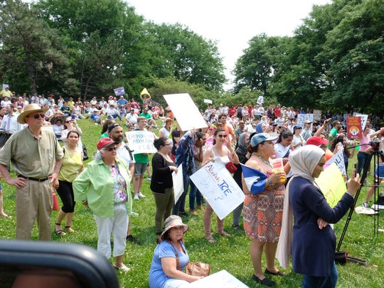 Hundreds gather at Clark Park to rally against the travel ban and family separation.
