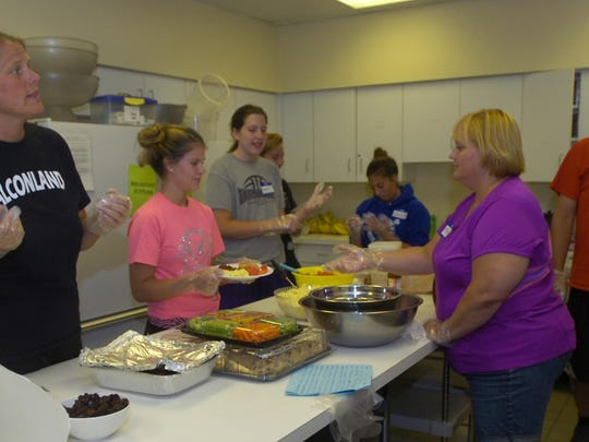 Mary Sheltrown, FHS athletic director, directs the process in the kitchen as students and parents help prepare dinner last Monday to serve to the homeless staying at North Congregational Church.