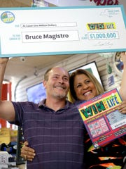 Bruce Magistro, left, and lottery representative Yolanda Vega pose for a picture during a news conference in Babylon, N.Y., Wednesday, May 11, 2016.