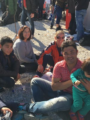 Kathy Marsh and Kristi Marsh visit with a refugee family in Lesbos.