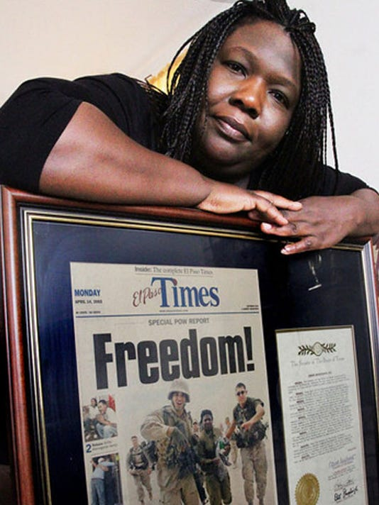 Shoshana Johnson shows a front page picture showing her rescue from Iraqi captivity. The picture frame hangs from above the fireplace of her living room.