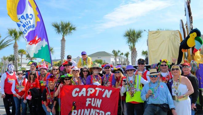 In their guise as the Krewe de Feet, members of Capt'n Fun Runners pose before the start of the 2015 Krewe of Wrecks Mardi Gras Parade on Pensacola Beach.