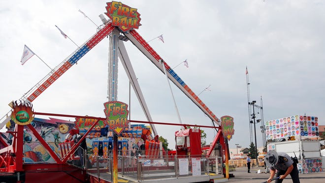 A trooper with the Ohio Highway Patrol removes a ground spike in front of the Fire Ball ride July 27, 2017, at the Ohio State Fair in Columbus, Ohio, the day after it broke apart, killing an 18-year-old and injuring seven others.