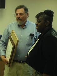 Francine Payton, right, receives a resolution from