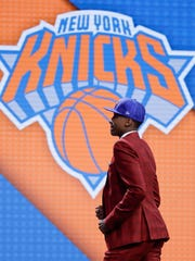 Frank Ntilikina walks up on stage after being selected
