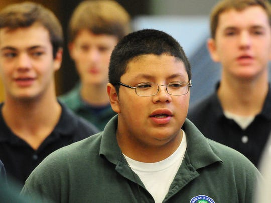 Notre Dame Academy sophomore David Torres sings during choir class last month.