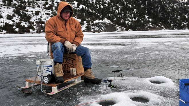 Bill Claassen keeps an eye on his poles while ice fishing at Holter Lake