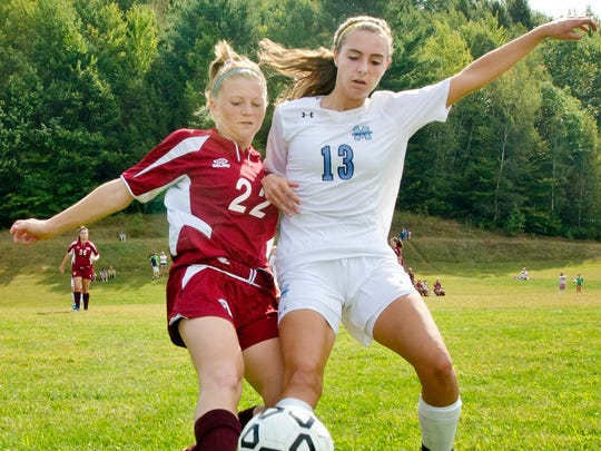 Mount Mansfield's Maddie Light, right, battles North Country Union's Ashley Robishaw-Morin along the sidelines during a game in Jericho.