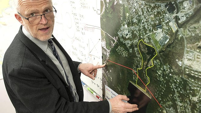Lawrence McKenna, a Framingham State University associate professor of physics and earth science, shows the proposed pipeline in Ashland, pictured in red, on a map in his office in April 2019.