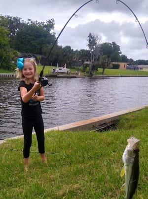 Maybrie Ronan, 7, holds up a snook that she caught using dead shrimp.
