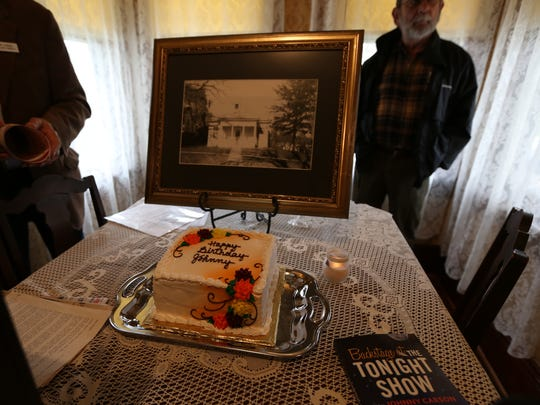 "A cake sits next to a historic picture of the the Johnny Carson birthplace at a birthday celebration for the television icon in Corning, Ia., in 2013. Carson hosted ""The Tonight Show."""