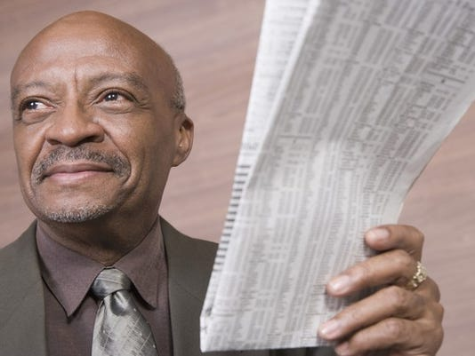 senior-businessman-holding-newspaper-with-stock-listings_large.jpg