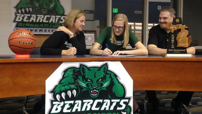 Payton Husson (middle) signs for Binghamton women's basketball with her parents, Stacey and Jerry, beside her.