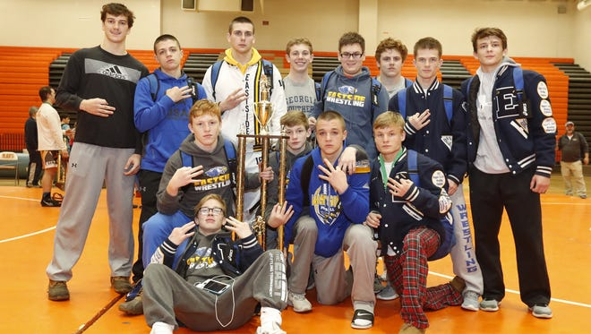 Eastside's wrestling team surrounds the championship trophy after winning the Greenville County tournament for the third consecutive year Saturday at Mauldin High School.