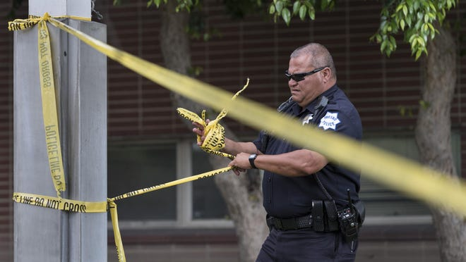 Fresno Police Officer John Pinedo gathers crime scene tape as police investigate an extensive crime scene in Downtown Fresno, Calif. on Tuesday, April 18, 2017