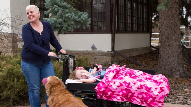 Melissa Kloiber, her daughter Jacey and Zoe the golden retriever wait for Great Falls Paratransit to arrive to transport Jacey to school for the afternoon.