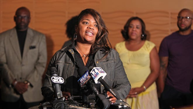 Flanked by supporters, Liz Rogers, owner of Mahogany's at The Banks, spoke to reporters just before closing the restaurant.