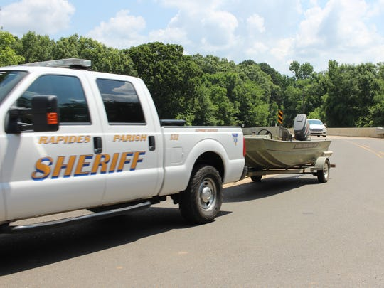 A Rapides Parish Sheriff's Office boat is taken down Rigolette Road Tuesday morning as a search for suspects who fled a Monroe armed robbery continues. One suspect was captured in Grant Parish, leaving two at large.