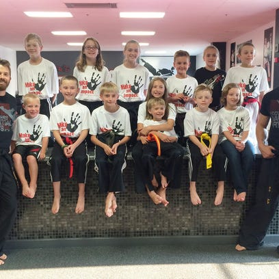 More than a dozen students of Hoover's Martial Arts in Brandon took part in the studio's Make An Impact program,which is now in its third year. Pictured are, from left, row one: Instructor Rob Green, Elias Horstmeyer, Noah Reyelts, Ronan Campbell, Sydney Campbell w/Hunter Campbell, Evan VanDeese, Rosie Leaverton and instructor Jordan Mitzel; row two: Connor Erickson, Madisyn Rust, Taylor Warner, Ryley McKeown, Kalli Reese and Rupert Leaverton.