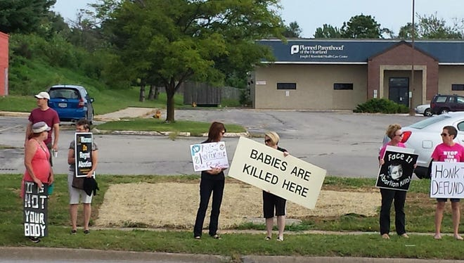 Protesters hold signs denouncing Planned Parenthood outside a south Des Moines clinic on Saturday, Aug. 22, 2015.