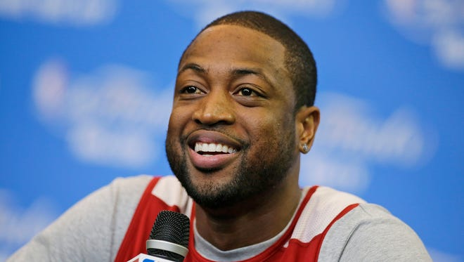 FILe - In this June 14, 2014 file photo, Miami Heat guard Dwyane Wade smiles as he is asked a question during a media availability for the NBA basketball finals in San Antonio. Signing day has arrived in the NBA, if the biggest free agents care to grab their pens. But it?s unclear if Carmelo Anthony, Chris Bosh and Dwyane Wade _ who all might be waiting on LeBron James to go first _ are ready. (AP Photo/Tony Gutierrez, File)