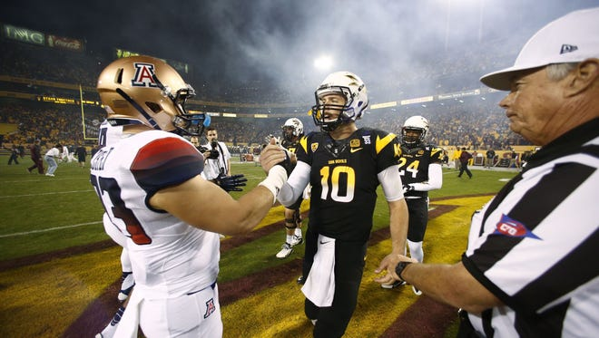 ASU quarterback Taylor Kelly greets Arizona linebacker Jake Fischer during the 87th Territorial Cup on Saturday, Nov. 30, 2013 in Tempe.