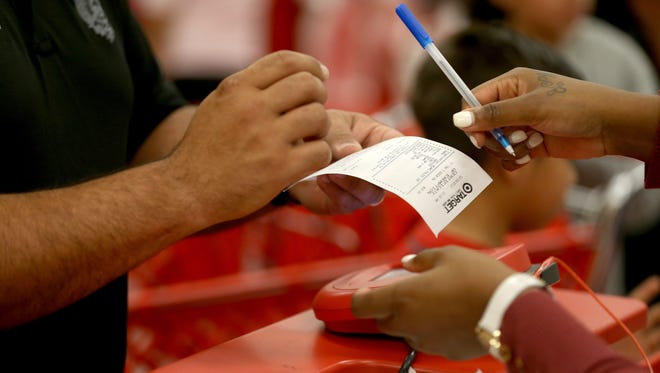 A customer prepares to sign a credit card slip at a Target store on Dec. 19 in Miami.