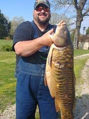 Powersite bowfisherman Casey Rains with his likely record 32.95-pound mirror carp.