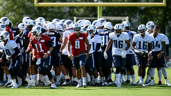 Titans quarterback Marcus Mariota (8) and his teammates take the field for practice on Friday.